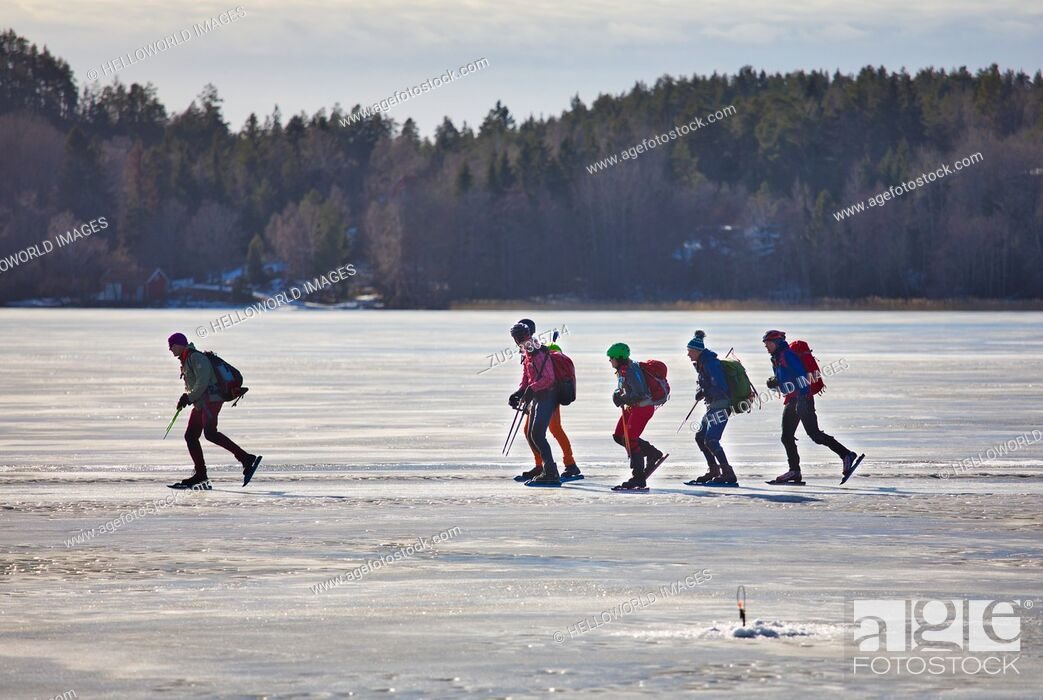 Stock Photo: Long distance ice skaters on Lake Malaren and in foreground unmanned ice fishing hole, Sigtuna, Sweden, Scandinavia.