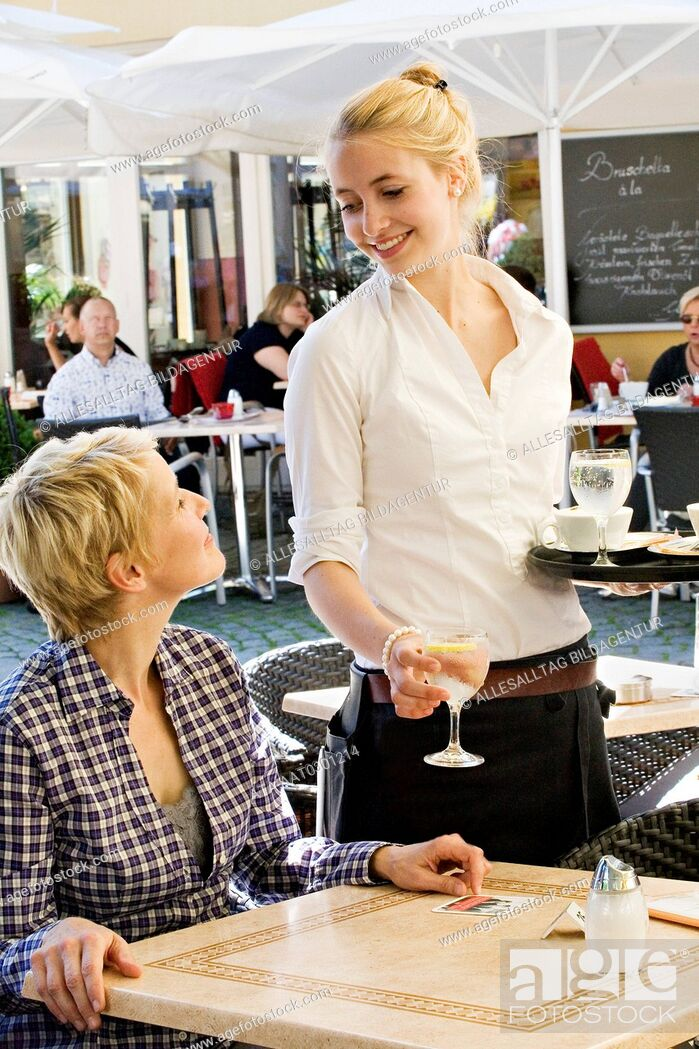 Stock Photo: Young waitress serving a customer.