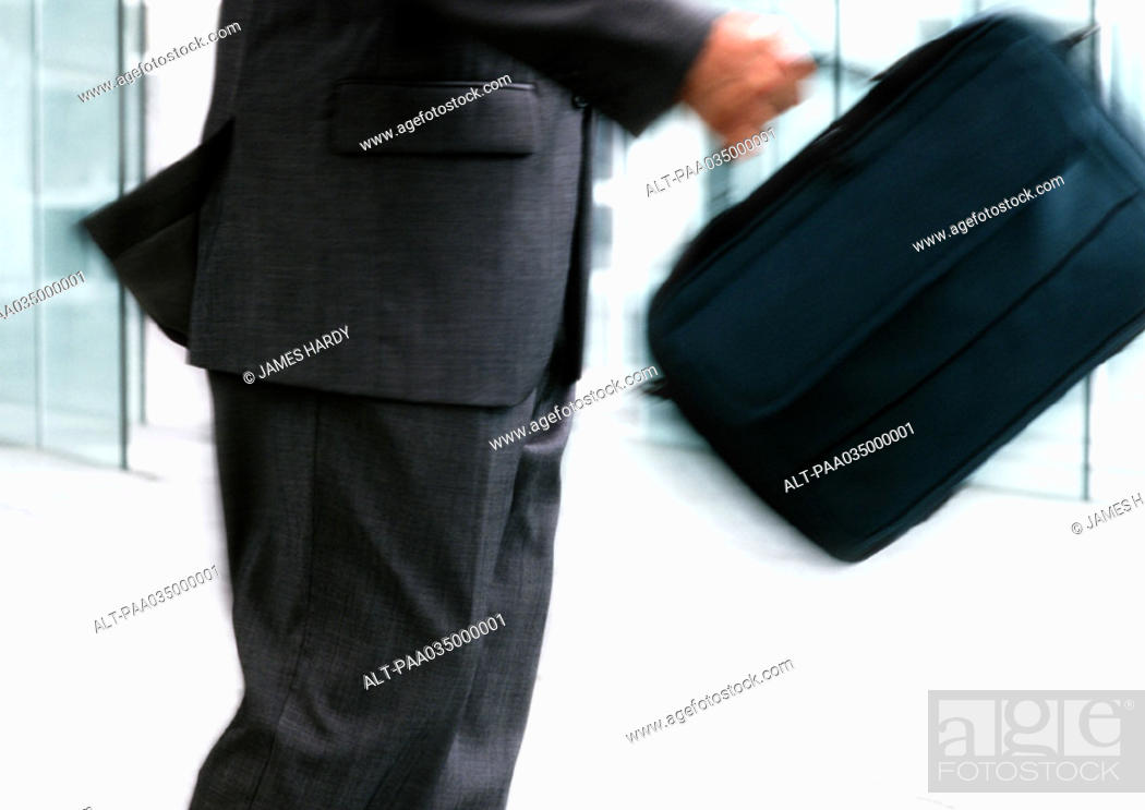 Stock Photo: Man holding bag, mid section, blurred motion.