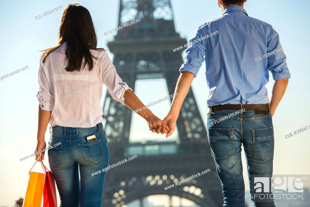 Stock Photo: Young couple strolling in front of Eiffel Tower, Paris, France.