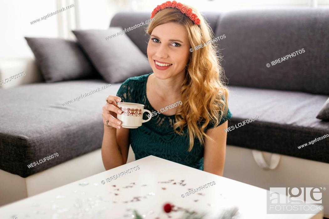 Stock Photo: Portrait of smiling young woman drinking coffee at home at Christmas time.