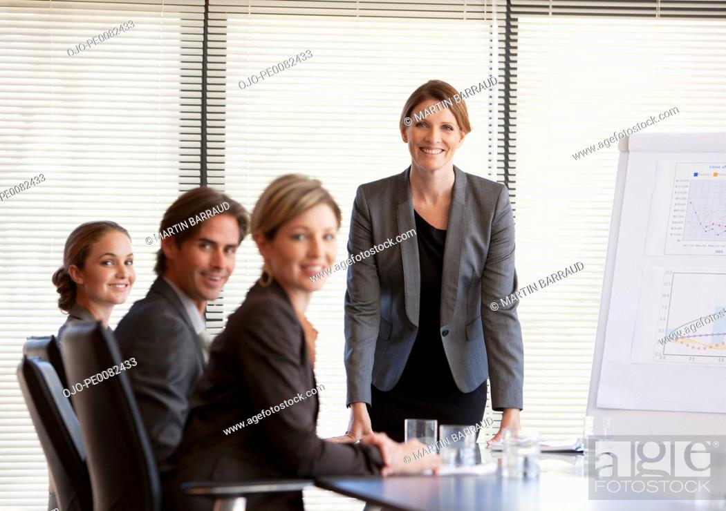 Stock Photo: Portrait of smiling business people meeting in conference room.