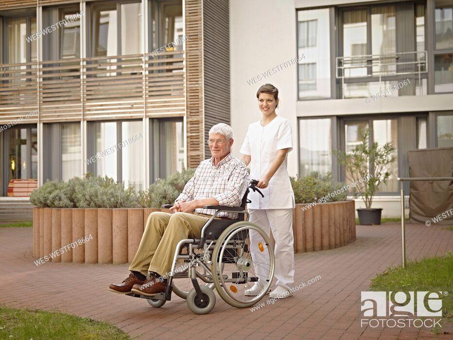 Stock Photo: Germany, Cologne, Caretaker pushing senior man in wheelchair outside of nursing home.