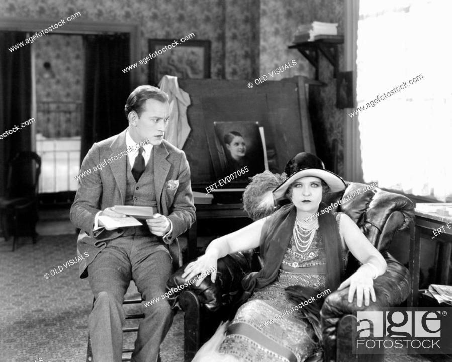 Stock Photo: Man and woman sitting in a living room reading a letter and looking surprised All persons depicted are not longer living and no estate exists Supplier.