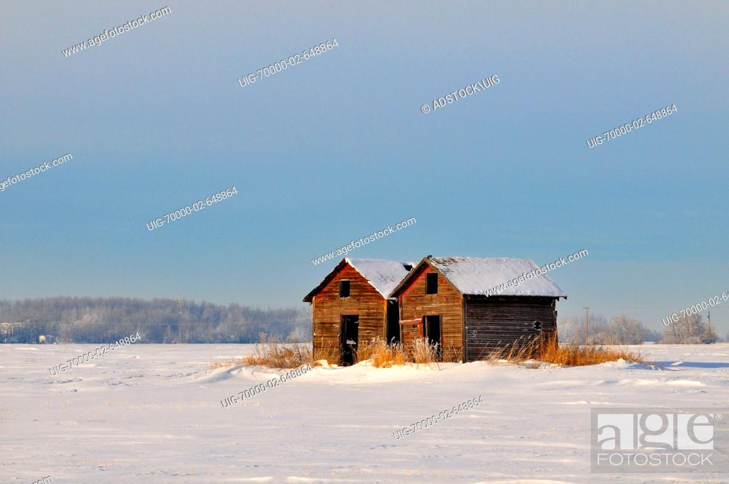 A horozontal winter scenic of two old type wwooden grain storage