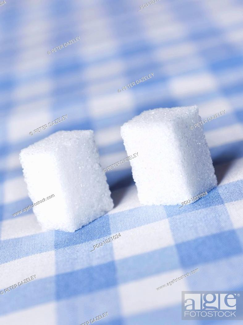 Stock Photo: Two sugar cubes on table cloth, close-up.