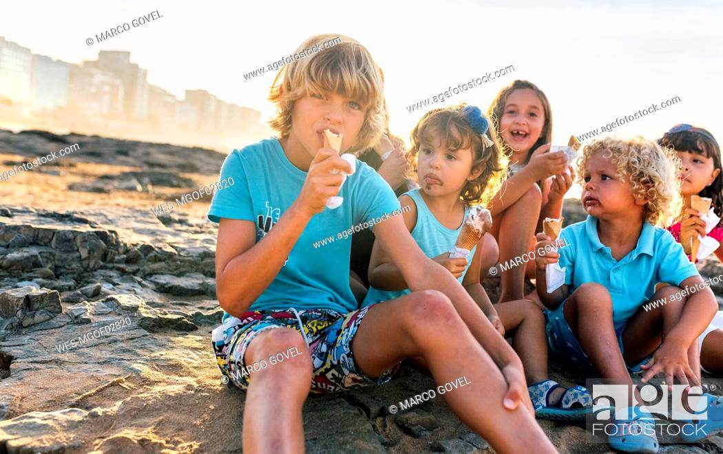 Stock Photo: Group of six children eating icecream on the beach.