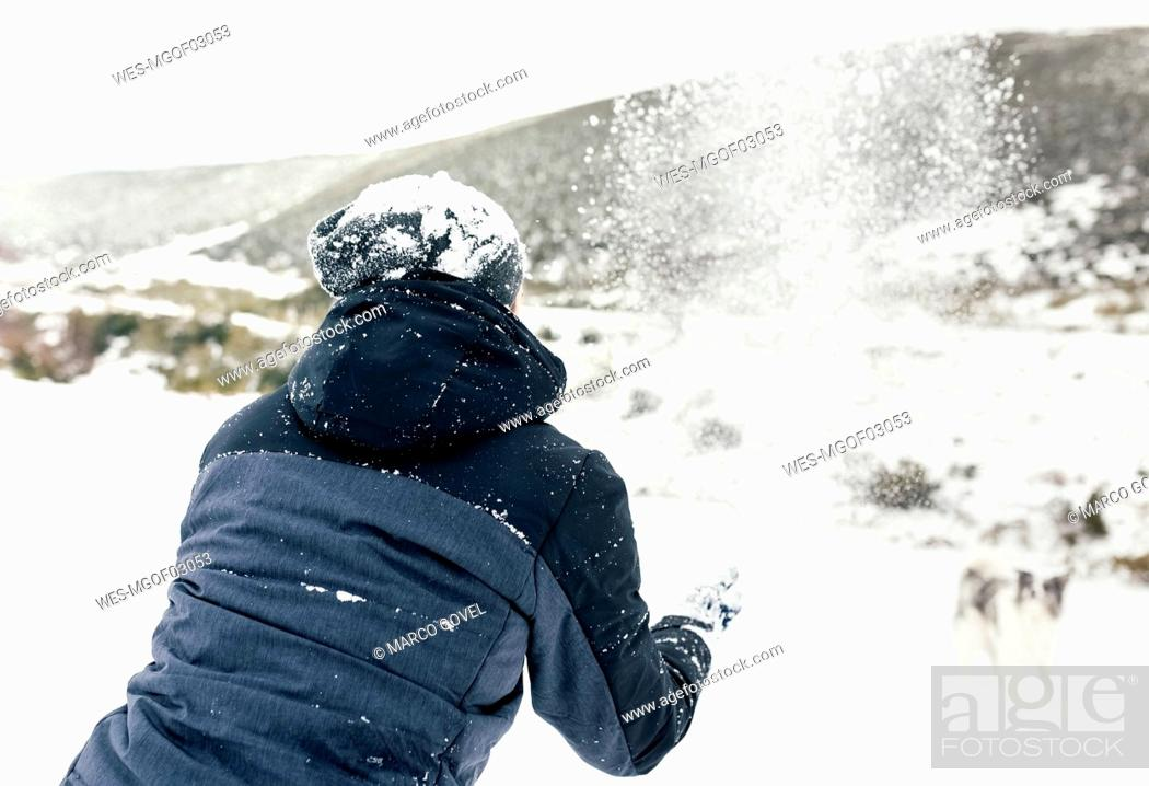Stock Photo: Young man playing with his dog in the snow.
