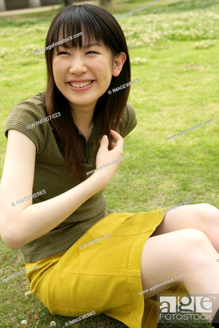 Stock Photo: A young woman in skirt sits on the grassland as she laughs her way to glory.