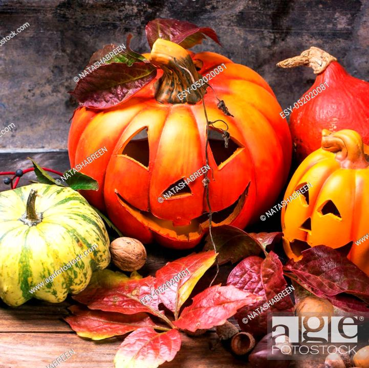 Stock Photo: Halloween's pumpkins with autumn leaves on wooden table. Square image with selective focus.