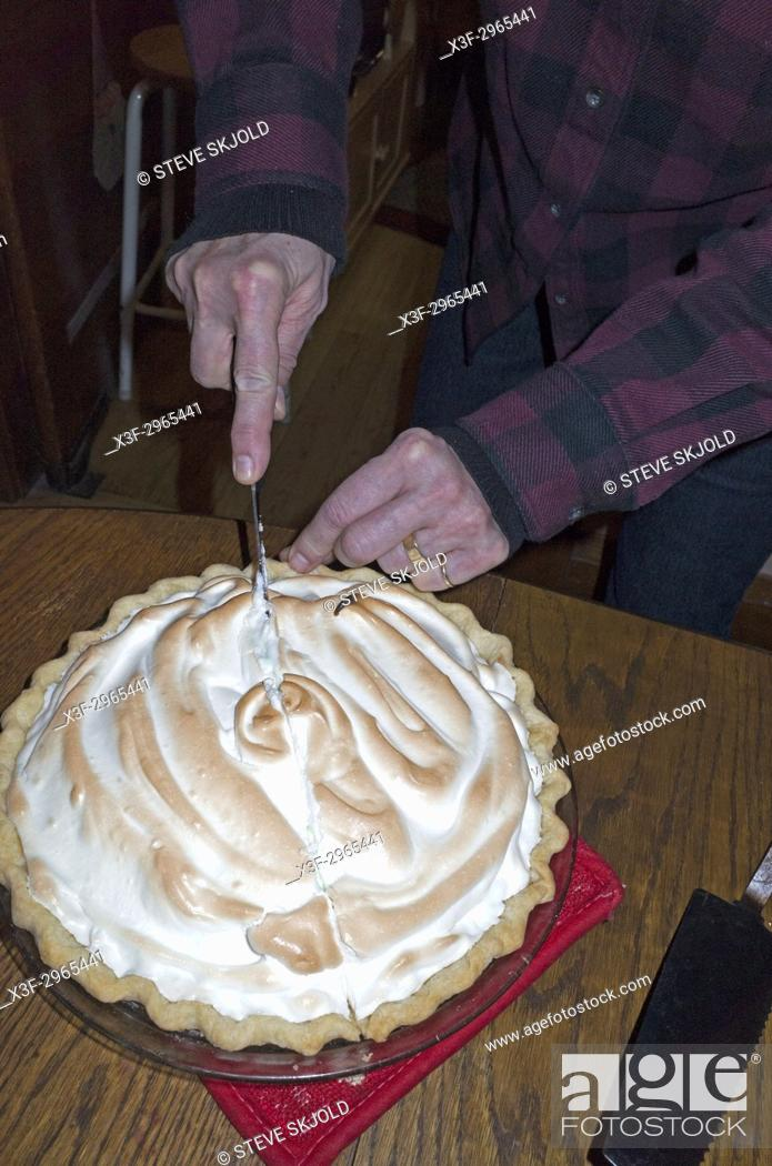 Senior man age 70 in plaid shirt cutting a piece of meringue topped