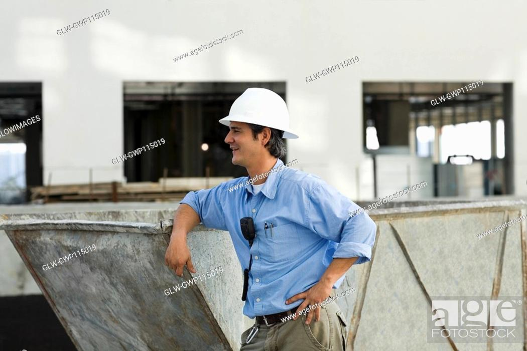 Stock Photo: Side profile of an engineer leaning against an industrial equipment.