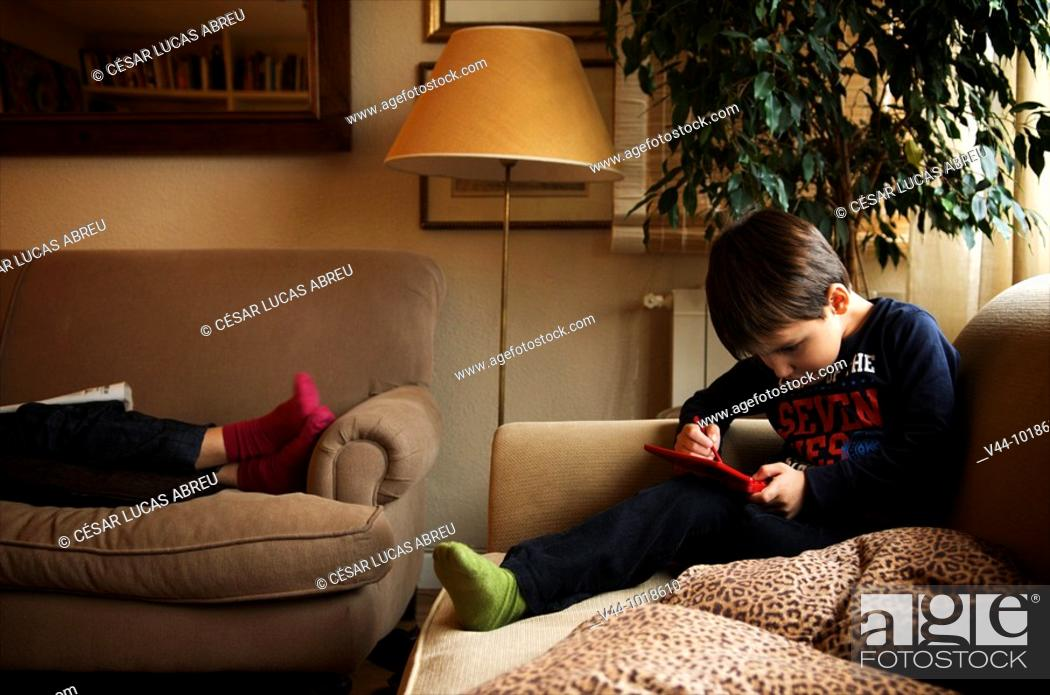 Stock Photo: Four years old kid playing electronic game at home  Madrid, Spain.