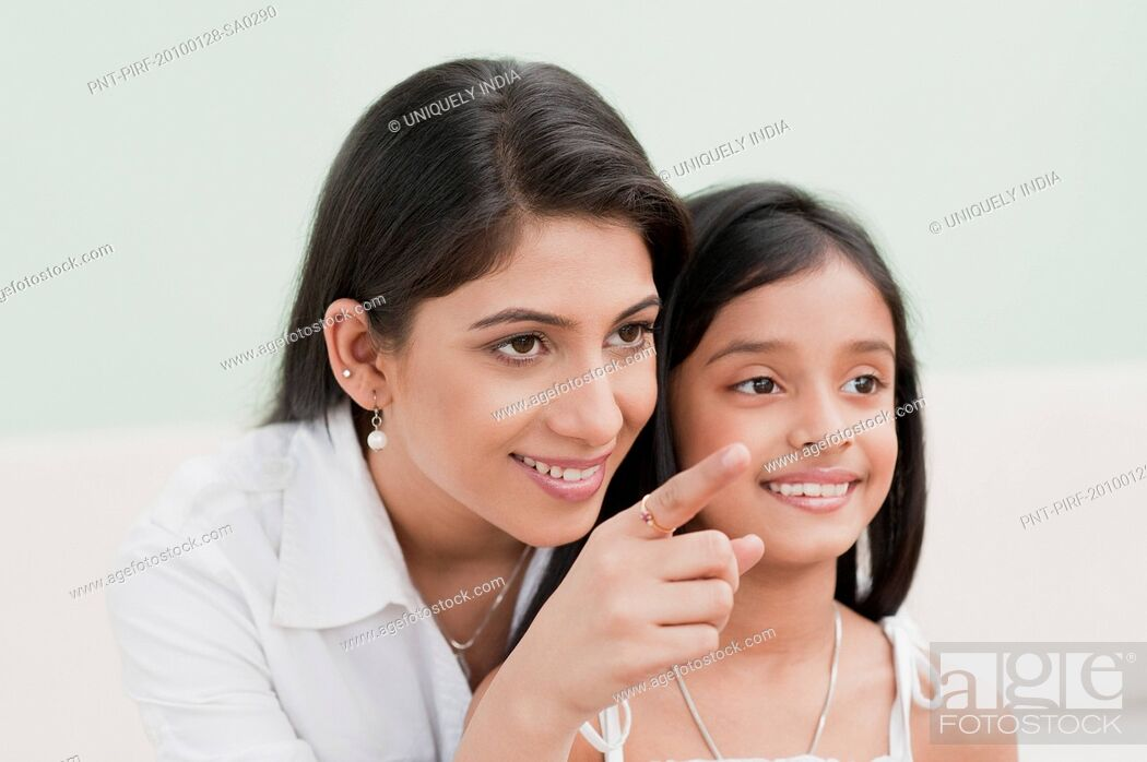 Stock Photo: Woman pointing away and smiling with her daughter.