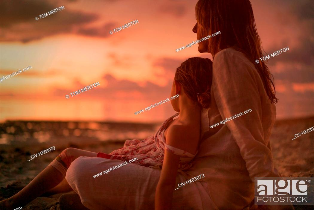 Stock Photo: Serene mother and daughter relaxing on beach at dusk.