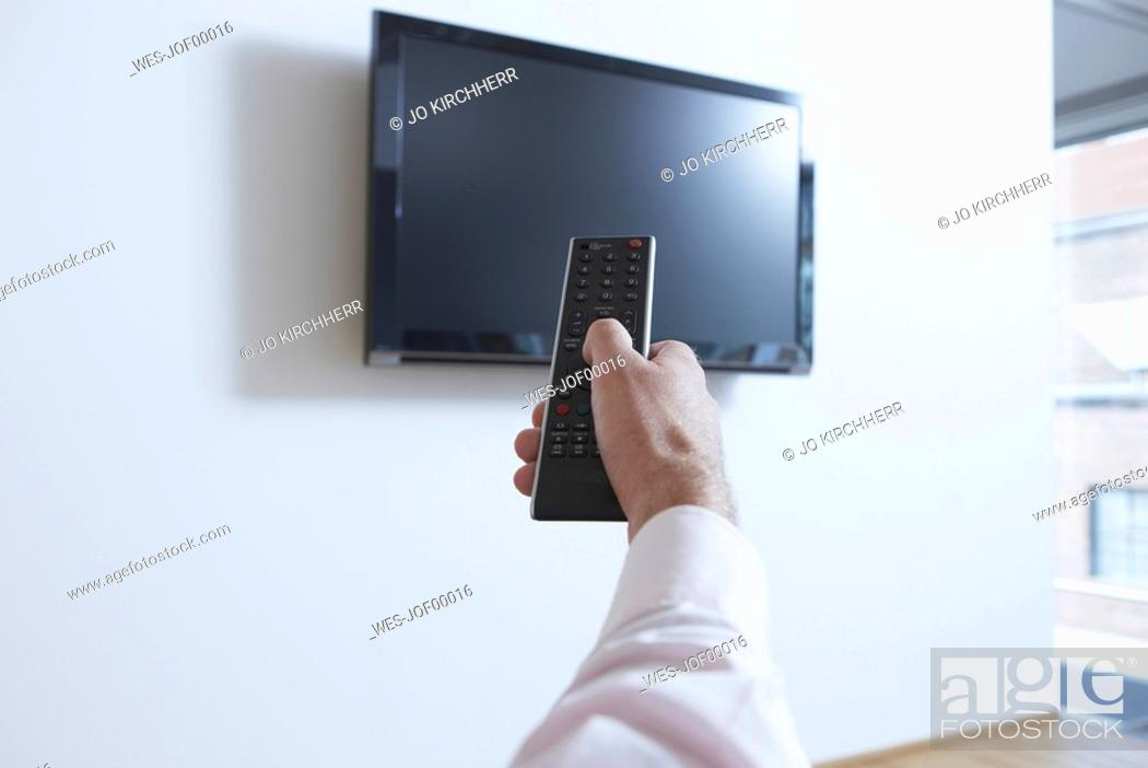 Stock Photo: Germany, Cologne, Person in office using remote control.