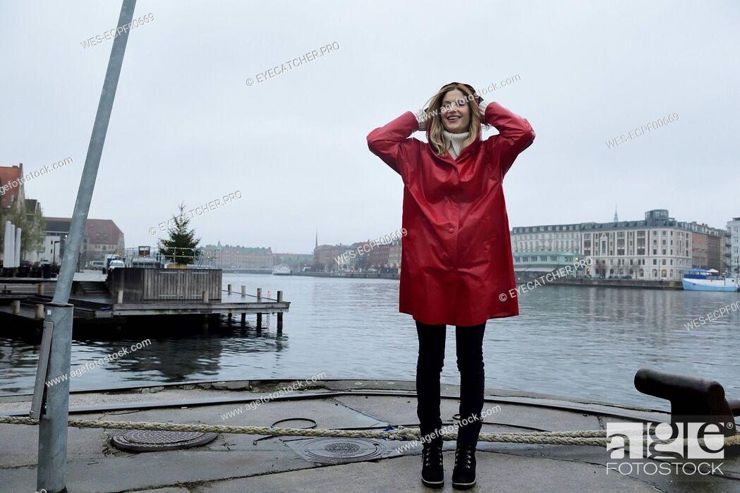 Stock Photo: Denmark, Copenhagen, happy woman at the waterfront in rainy weather.