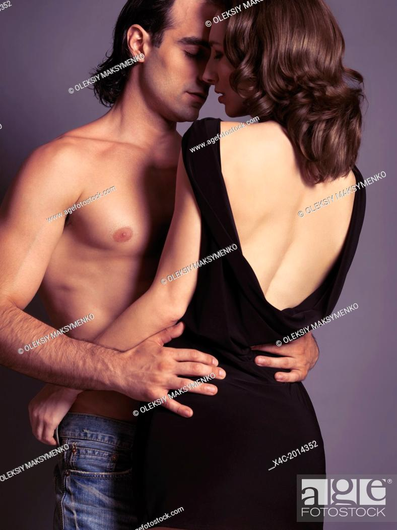 Stock Photo: Sensual portrait of a young sexy couple about to kiss. Man with bare torso embracing a woman in dress with open low back. Isolated on gray background.