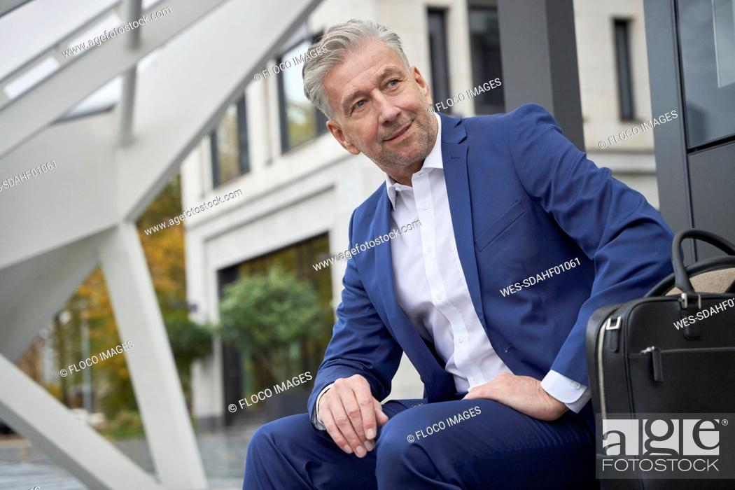 Stock Photo: Senior male entrepreneur looking away while waiting at bus stop in city.