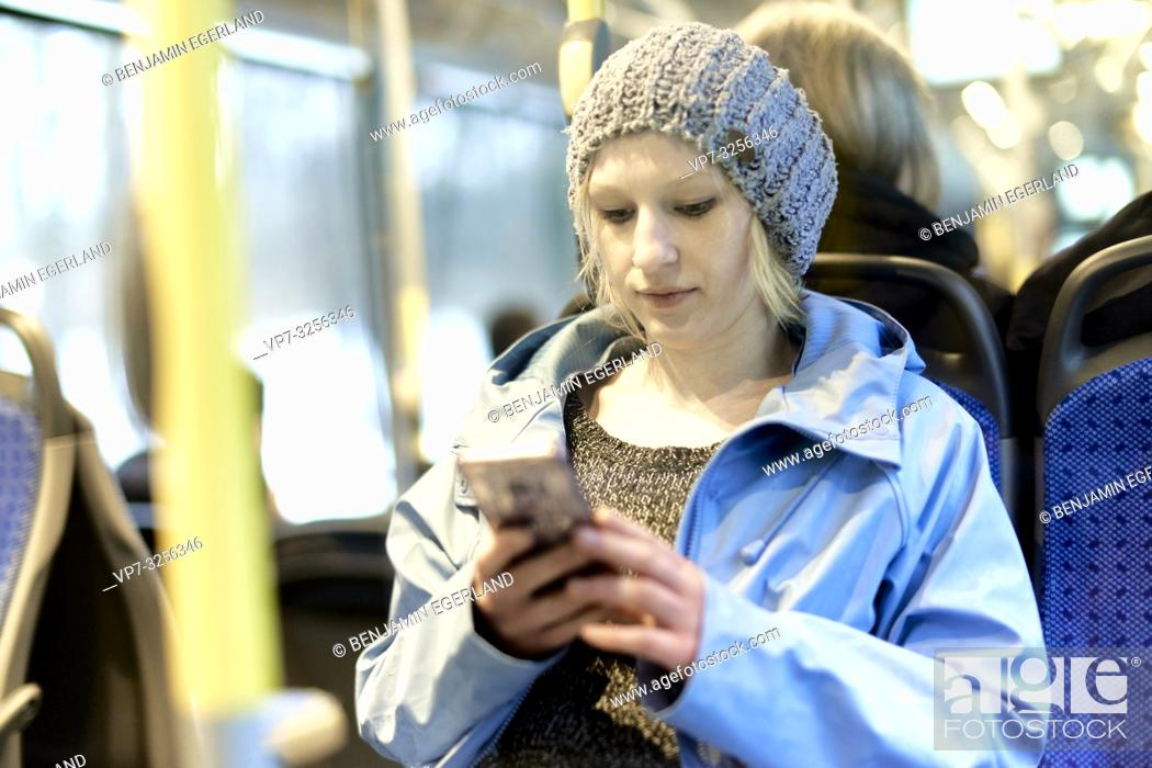 Imagen: Young woman using phone in bus, Munich, Germany.