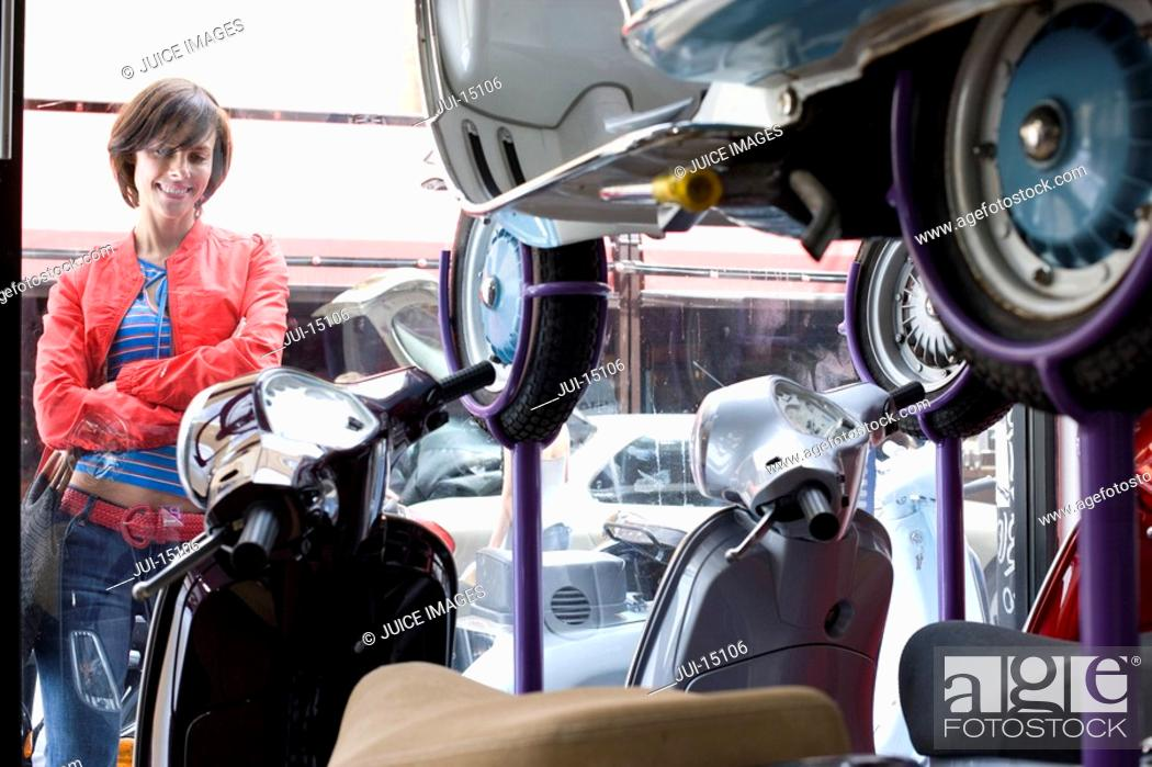 Stock Photo: Woman looking at scooters in shop.