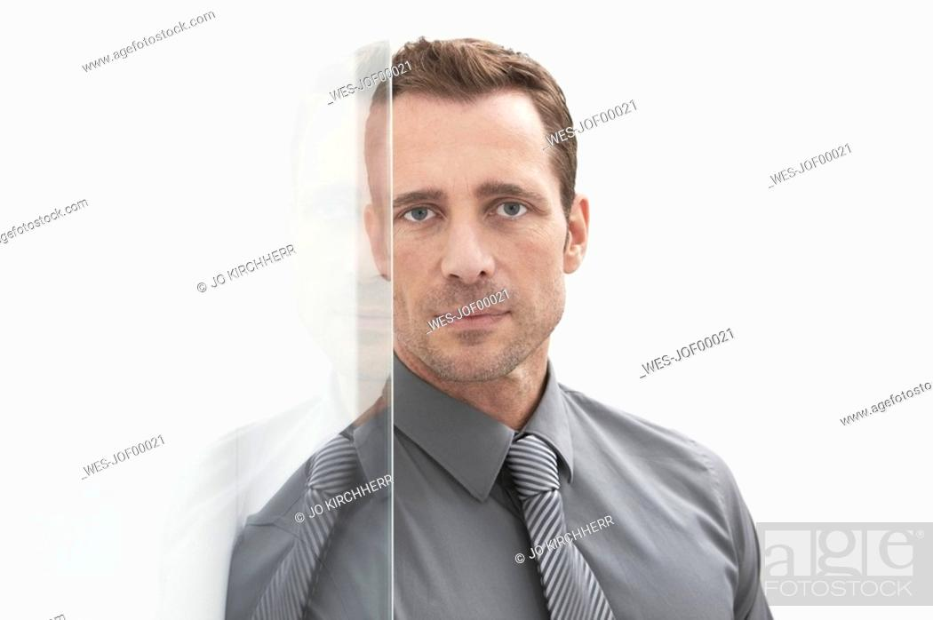 Stock Photo: Germany, Cologne, Businessman standing next glass door, portrait.