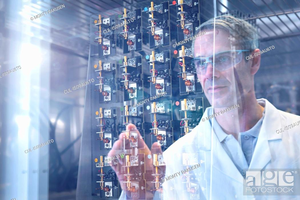 Stock Photo: Scientist inspecting test lithium ion batteries in heat chamber in battery research facility.