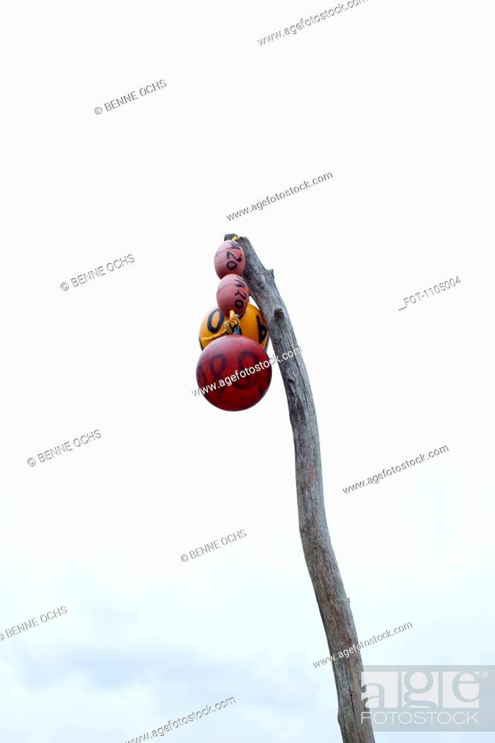 Stock Photo: Low angle view of buoys hanging from a wooden post.