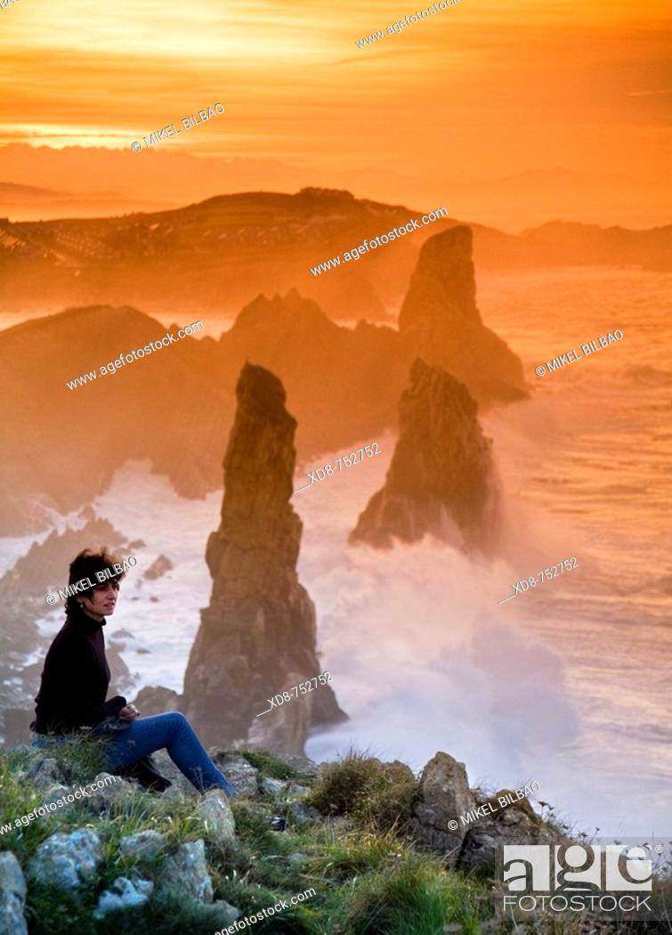 Stock Photo: young woman looking from a rocky coast  Liencres, Cantabria, Spain, Europe.