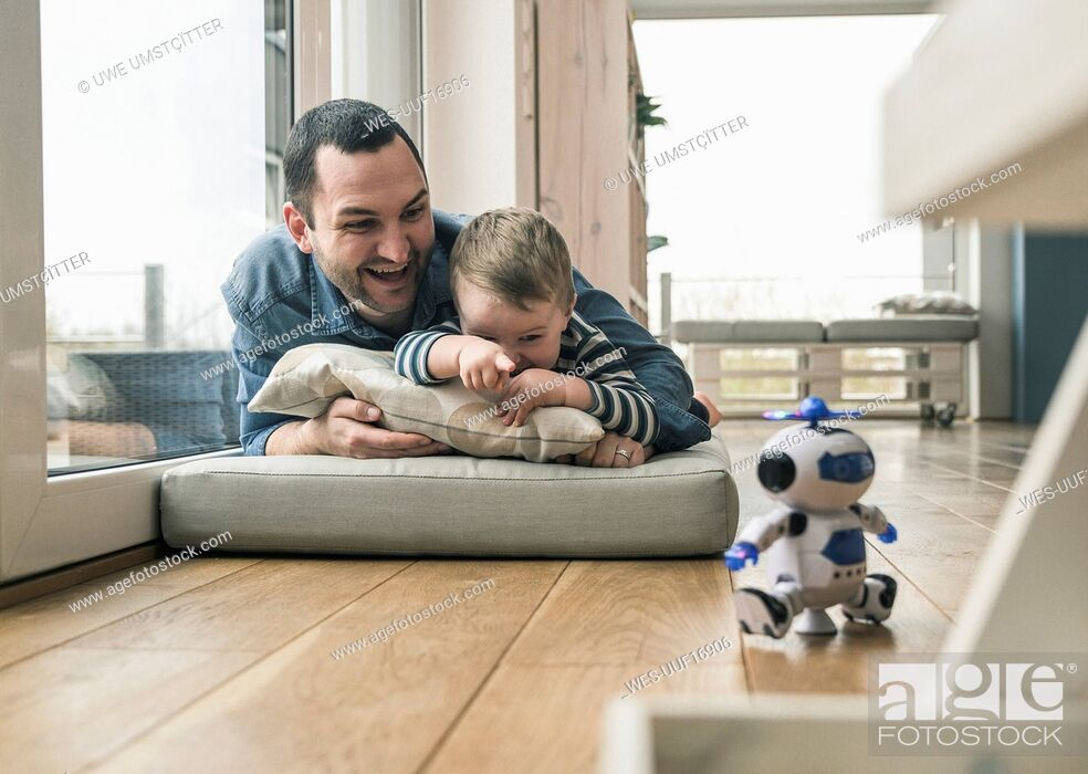 Stock Photo: Excited father and son lying on a mattress at home watching a toy robot.