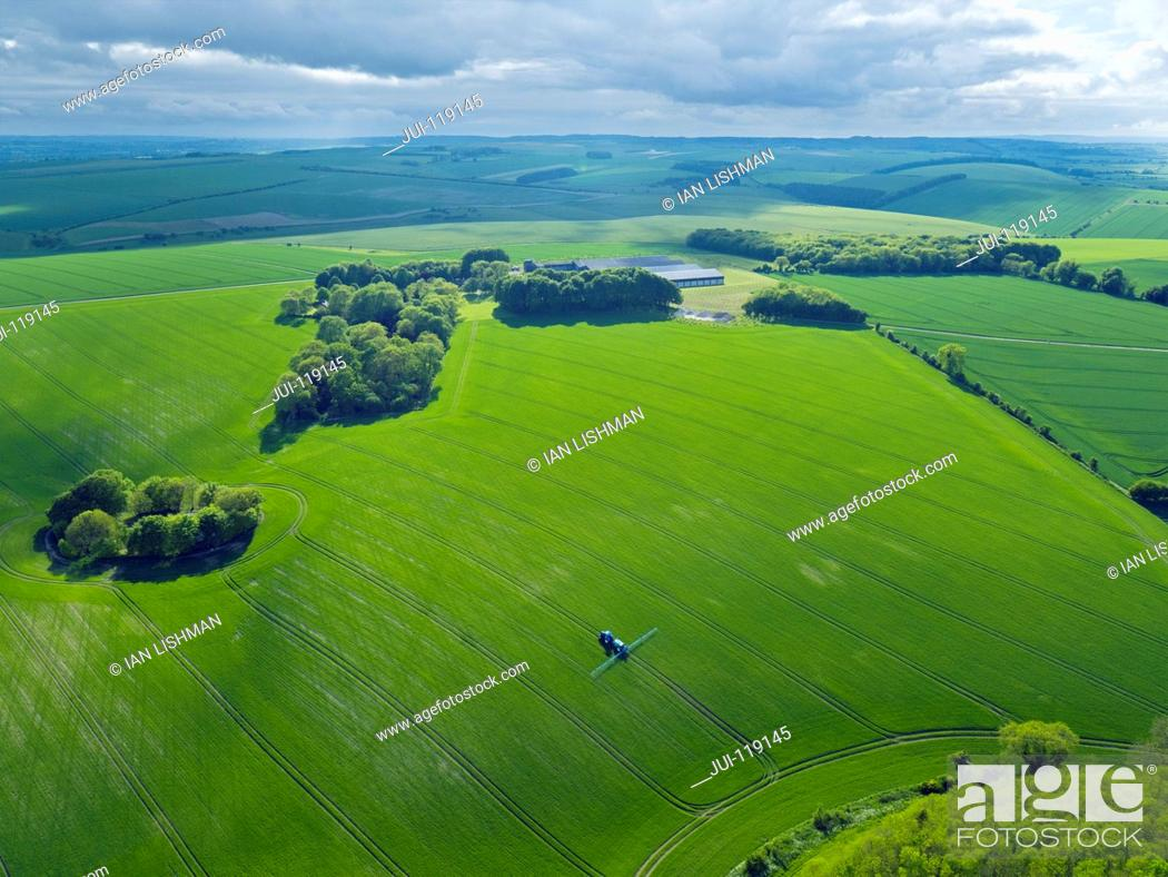 Stock Photo: Aerial view of tractor spraying crop in green farm fields with pesticide.