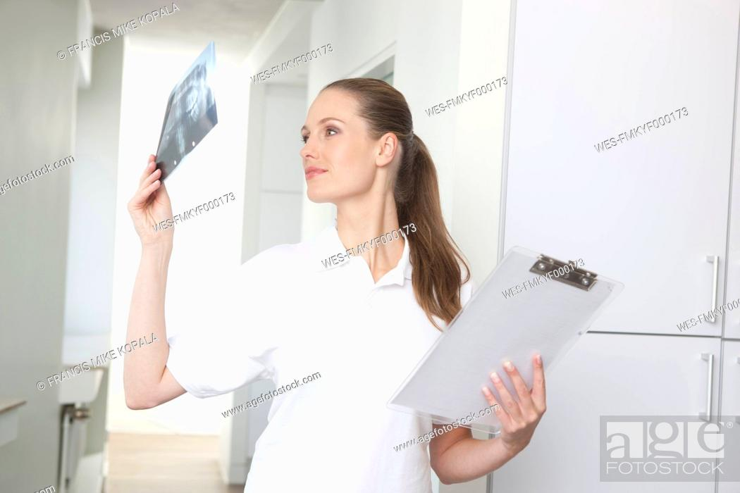 Stock Photo: Germany, Dentist looking at dental x-rays.