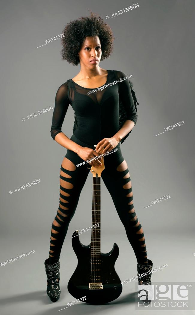 Photo de stock: beautiful black girl with angel wings and electric guitar, studio shooting.