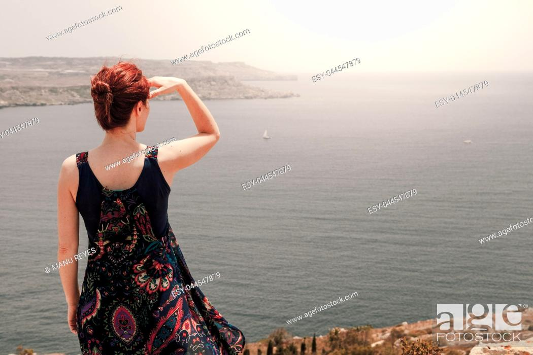 Stock Photo: Young redhead woman with a topknot looking far away the sea with her hand over head from a cliff with her long dress moving with wind.
