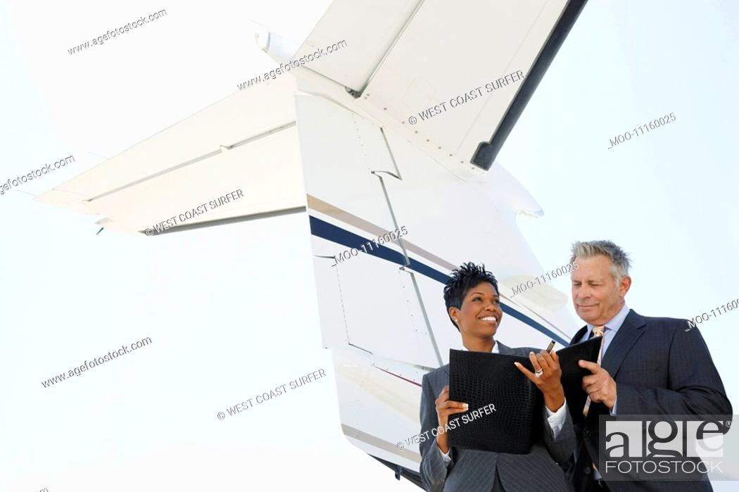 Stock Photo: Businesspeople standing below wing of private jet low angle view.