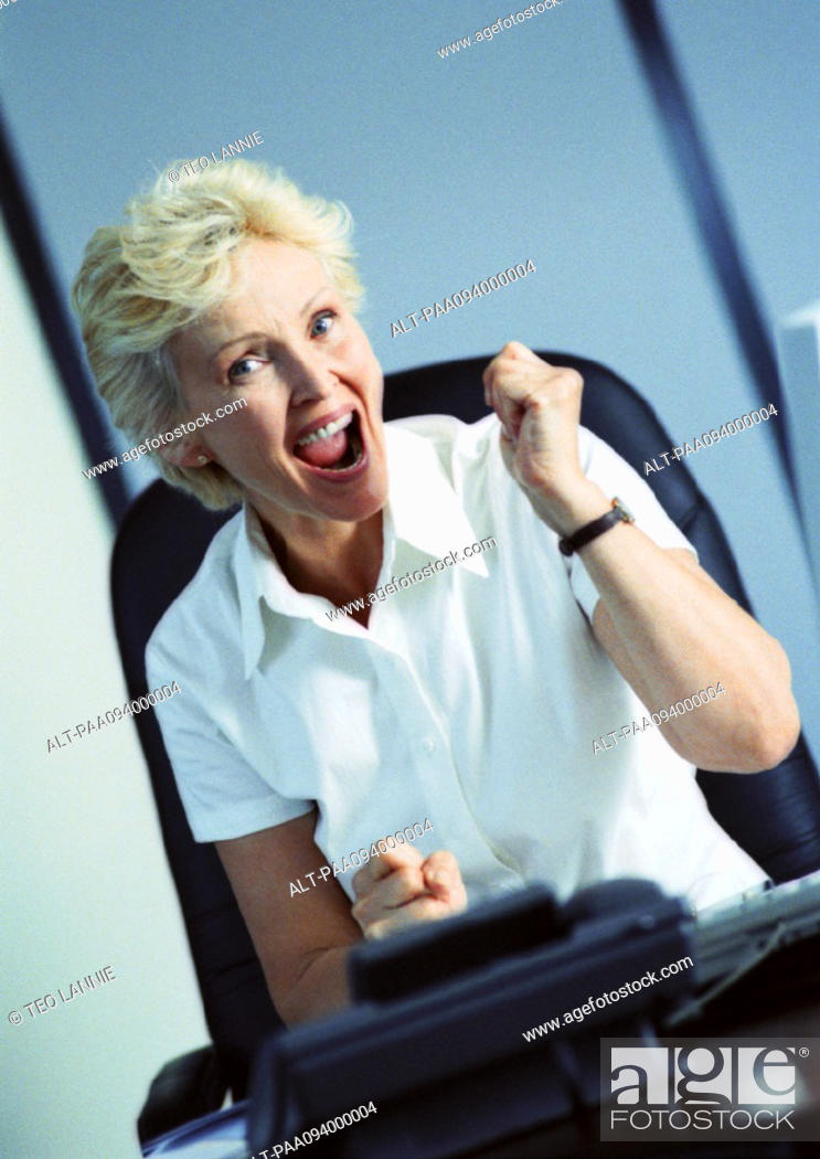 Stock Photo: Businesswoman raising fist and smiling, portrait.