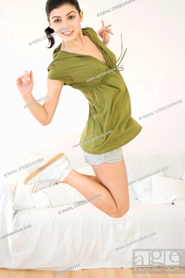Stock Photo: happy young woman jumping.