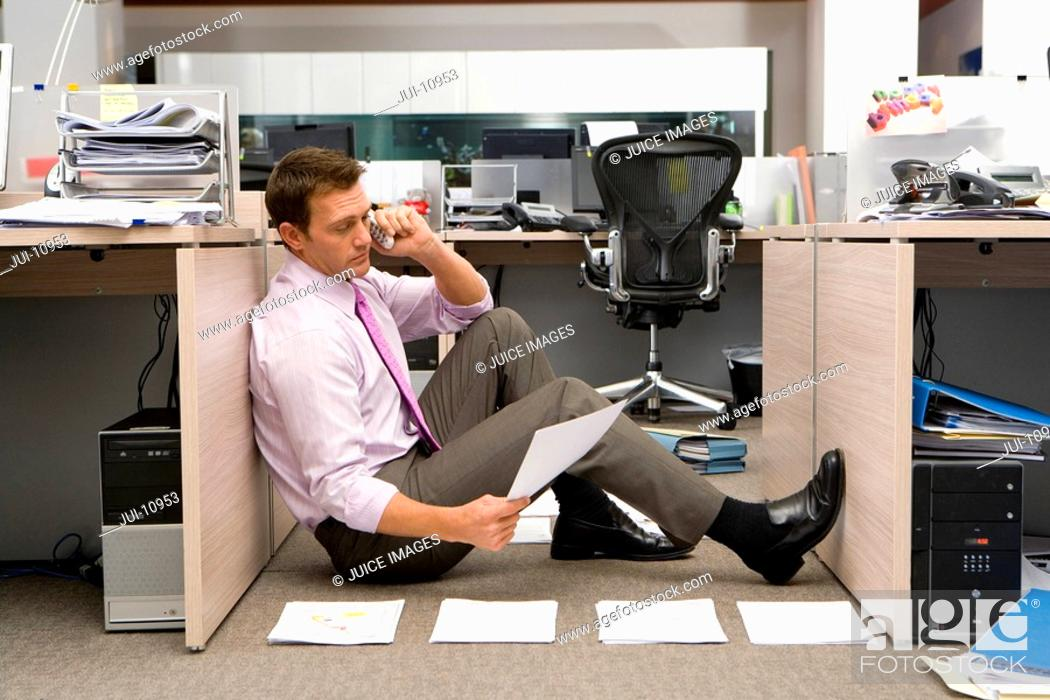 Stock Photo: Businessman sitting on floor by piles of paperwork, using telephone, side view.
