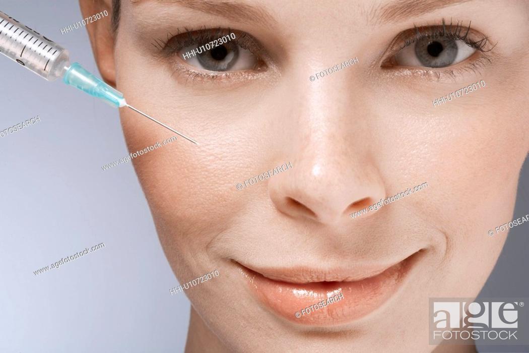 Stock Photo: Syringe near woman's face, close-up.