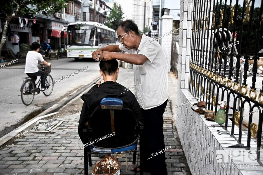 Stock Photo: A barber cuts the hair on the street. Shanghai, China.