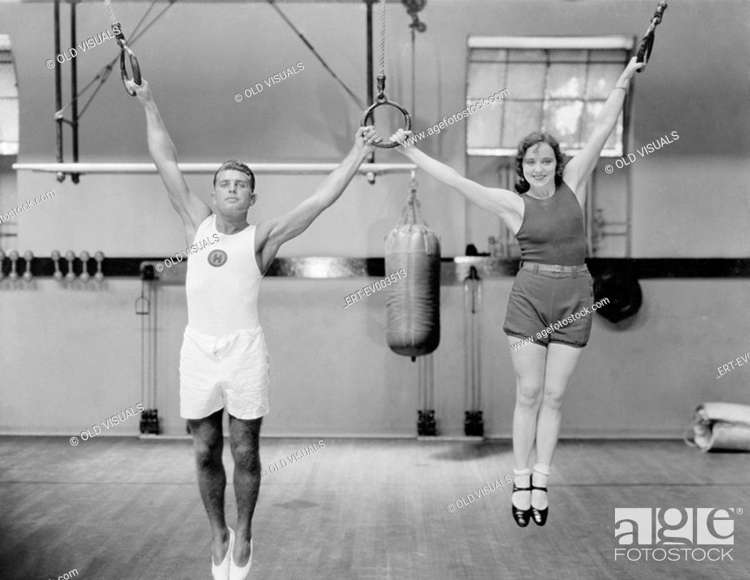 Stock Photo: Athletes on rings in gym All persons depicted are not longer living and no estate exists Supplier warranties that there will be no model release issues.