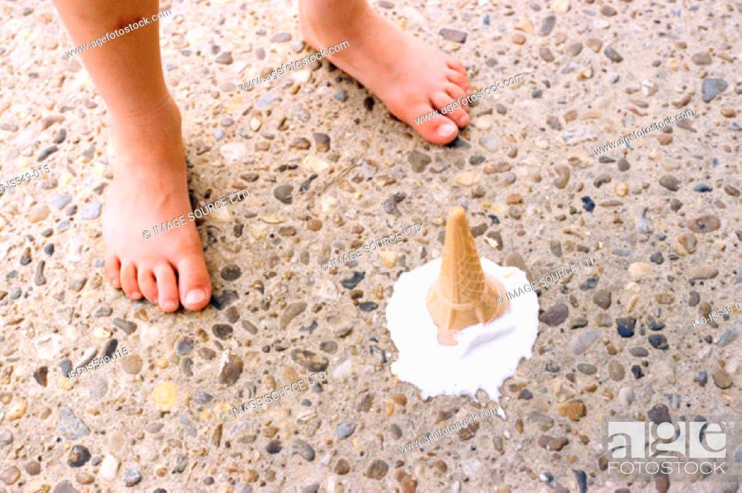 Stock Photo: Melting ice cream by child's feet.
