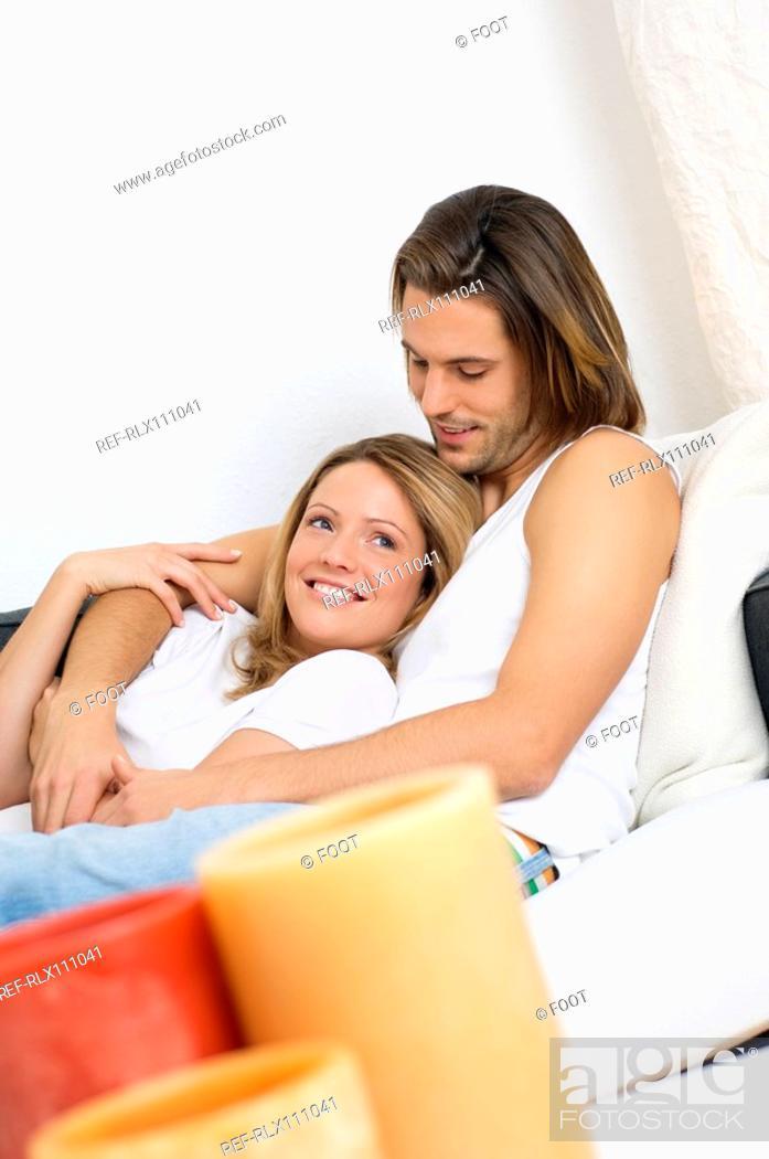 Stock Photo: Young couple lying on sofa.