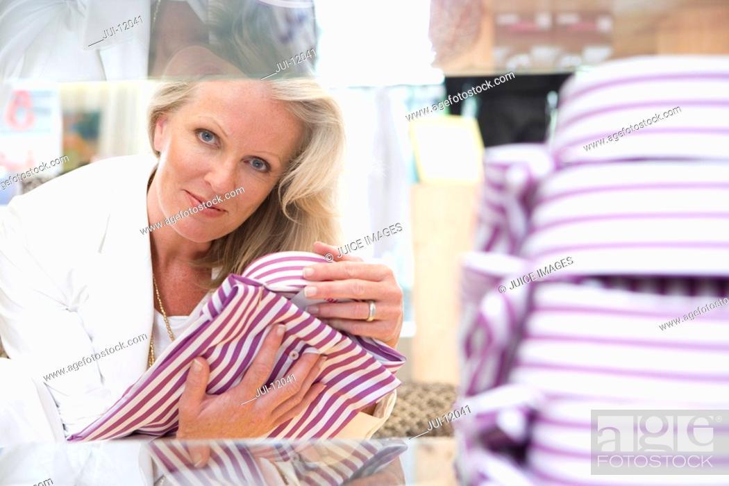 Stock Photo: Mature female shop assistant adjusting shirt for display, portrait.