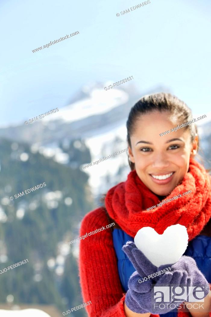 Stock Photo: Portrait of smiling woman holding heart-shape snowball.