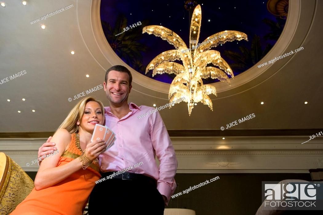 Stock Photo: Young couple in casino, woman with hand of cards, smiling, portrait.