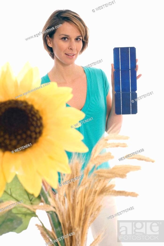 Stock Photo: Woman holding solar cells, sunflower in foreground.