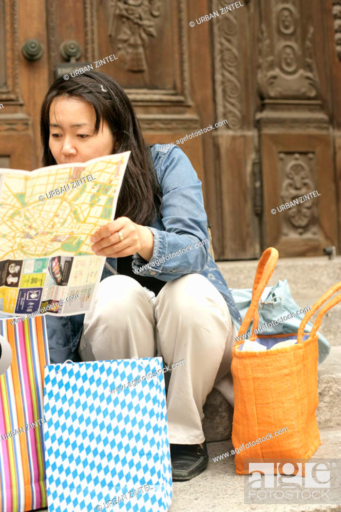 Stock Photo: Young Asian woman with a map sitting in front of a wooden door of a church.