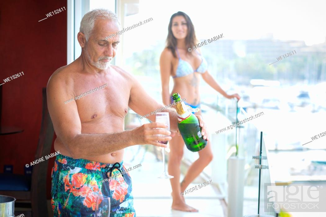 Stock Photo: Older caucasian man pouring sparkling wine into glass for younger woman.