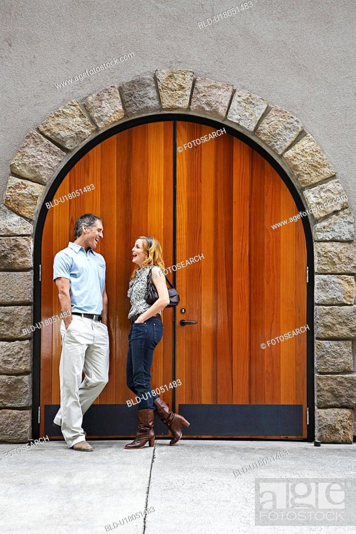 Stock Photo: Mid Adult Couple Talking by Arched Door.